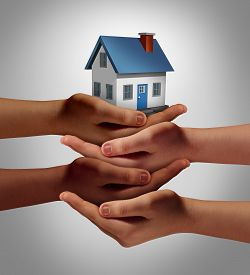 stock photo of social housing  - Community housing concept and neighbor support or neighborhood watch symbol as a connected group of diverse hands supporting and holding a family home as a metaphor for friendly residents - JPG
