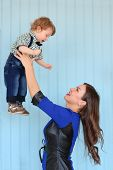 stock photo of throw up  - Beautiful woman in blue dress throws up little son in light blue room - JPG