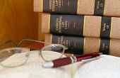 stock photo of law-books  - law books in a stack with glasses and pen on book - JPG