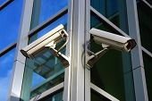 two security cameras on the glass facade