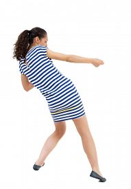 picture of roping  - back view of standing woman pulling a rope from the top or cling to something - JPG