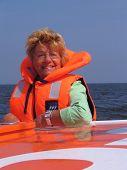 Lady In Orange Against A Blue Sky On A Boattrip