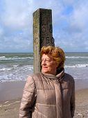 Mujer apoyado contra un poste