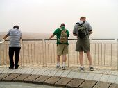 Tourists Looking At Mountains Of Sand In Massada/Israel poster