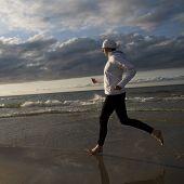 Beautifull woman running on the beach at sunset
