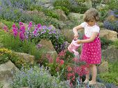 Cute girl watering flower in the garden