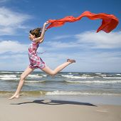 Happy girl jumping with scarf on the beach.