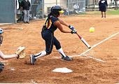 image of fastpitch  - Fastpitch softball girl having made contact with softball flying off the bat - JPG