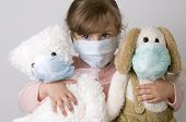 Little girl with toys wearing a protective mask