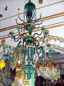 stock photo of imambara  - Centuries old beautiful ornate candle chandlier hanging from the roof of famous tourist attraction and palce of worship a husainia or imabara for shia moslems - JPG