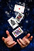 hands of a magician with cards floating over a space background
