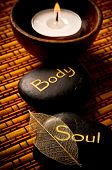massage stones - relax, body, soul - and a candle over bamboo background like a concept for wellness
