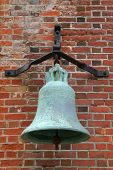 Very old bronze 17th century bell on a bracket situated on the wall of a coastal fortress built by H