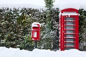 A traditional red English public phone and post box after a heavy snow fall.