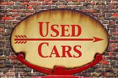 A rusty old retro arrow sign with the text Used cars