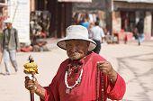 Elderly pilgrim in buddhist temple,  Kathmandu, Nepal