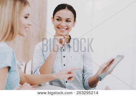 poster of Beautiful Brunette And Blonde. Reception Workplace. Workplace In Beauty Salon. White Interior. White