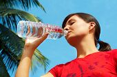 Beautiful girl drinking pure water against blue sky