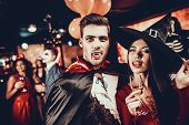 Young Happy Couple In Costumes At Halloween Party. Handsome Man And Beautiful Woman Drinking Champag poster