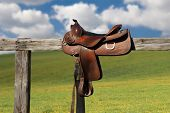 stock photo of saddle-horse  - Horse saddle on rural fence - JPG
