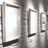 Three frames on white wall in museum
