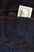 Mobile phone and one dollar banknote in jeans pocket