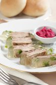 Beef tongue in aspic with horseradish on white plate closeup