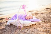 Little Girl On Sea Beach. Baby Is Wearing In Lilac And Lavender Dress. Infant Lies In Wicker Basket  poster