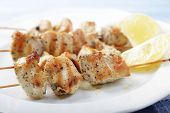 picture of souvlaki  - Chicken souvlaki on wooden skewers with lemon - JPG