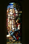 Stained glass window of an angel presenting a head garland of leaves to a young soldier, possibly Jo