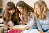 Three girls learning from books.
