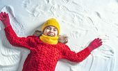 Happy child girl playing on a winter walk in nature. Kid making snow angel. poster
