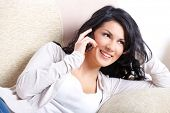 Beautiful young Woman talking on the Phone auf dem sofa