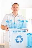 Happy man holding bin full of plastic blue bottles