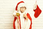 Young Cute Santa Claus Boy With Glasses In Red Sweater And New Year Hat Showing Cool And Holds Decor poster