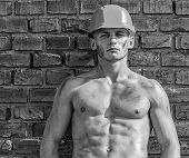 Builder With Muscular Torso And Helmet, Brick Wall On Background. Hard Worker Concept. Athlete With  poster