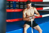 Smiling Boxer Wrap Hands With Boxing Wraps. Fighter Behind Ring Preparing For Fight. Protection Conc poster