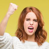 Young beautiful woman over isolated background wearing winter sweater angry and mad raising fist fru poster