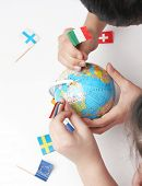 children pointing flags on world globe
