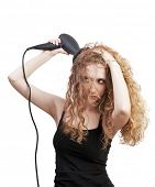 blond woman drying her hair with professional hair-dryer; beauty salon