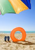 holiday background; orange ring buoy blue slippers and colorful umbrella on the beach in summer
