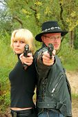 Women And Man Back-to-back Aiming Handguns