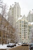 City in winter: snow-covered trees, cars, roadway and white multistorey building at the end of the s