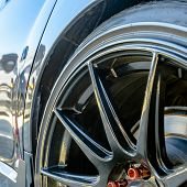 Shiny Car With Black Mag Wheel And Red Lug Nuts poster