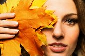 Close-up of woman face and autumn leaves