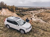 Couple Standing Near Suv Car At The Cliff With Beautiful View From The Top. poster