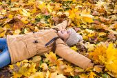 Cute Happy Little Girl Lying On The Fallen Leaves Arms Outstretched And Holding The Bouquets Of Yell poster