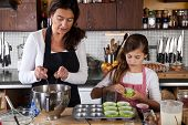 stock photo of mother child  - Mother and daughter filling cupcakes in kitchen - JPG