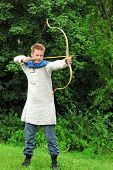 stock photo of longbow  - young man Aiming Bow - JPG