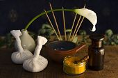 stock photo of vedic  - An arrangement of turmeric spice oil bowl and bottle and massage poultice boluses used in Ayurveda massage with an exotic flower and incense burning in the background - JPG